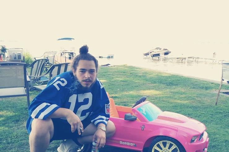 Post Malone posing next to a four wheeler car toy