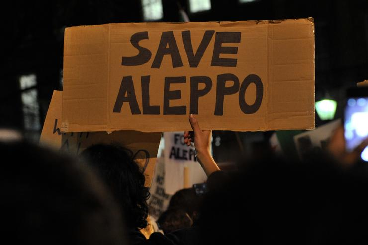 Protesters hold placards during a demonstration in solidarity with the inhabitants of the embattled Syrian city of Aleppo, outside the entrance to Downing Street, in central London on December 13, 2016. Civilians and rebel fighters were to start evacuating from Syria's Aleppo 'within hours' under a deal reached Tuesday that would end years of opposition resistance in the city. Rebel officials, Russia and Turkey confirmed the agreement which, if implemented, would mark a major victory for President Bashar al-Assad over opposition forces who rose up against him in 2011.