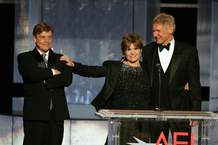 Actors Mark Hamill, Carrie Fisher and Harrison Ford speak onstage during the 33rd AFI Life Achievement Award tribute to George Lucas at the Kodak Theatre on June 9, 2005 in Hollywood, California.