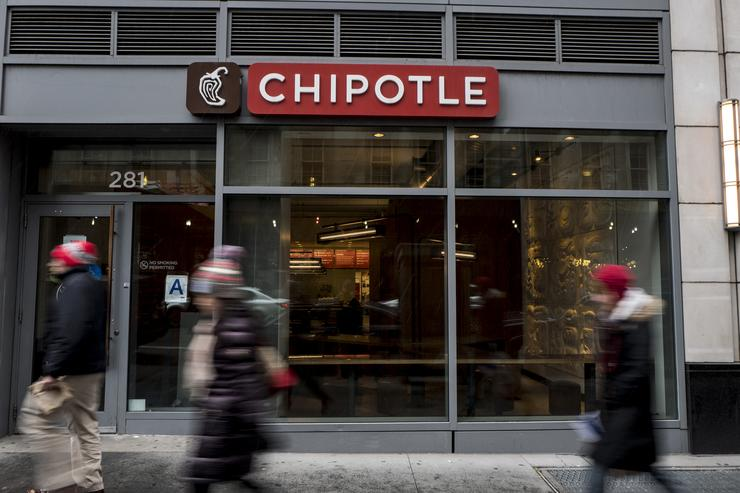 People walk past a Chipotle restaurant on Broadway in Lower Manhattan on February 8, 2016 in New York City. The Mexican food chain is closing stores for lunch nationwide for a meeting on food safety following a number of E. coli outbreaks.