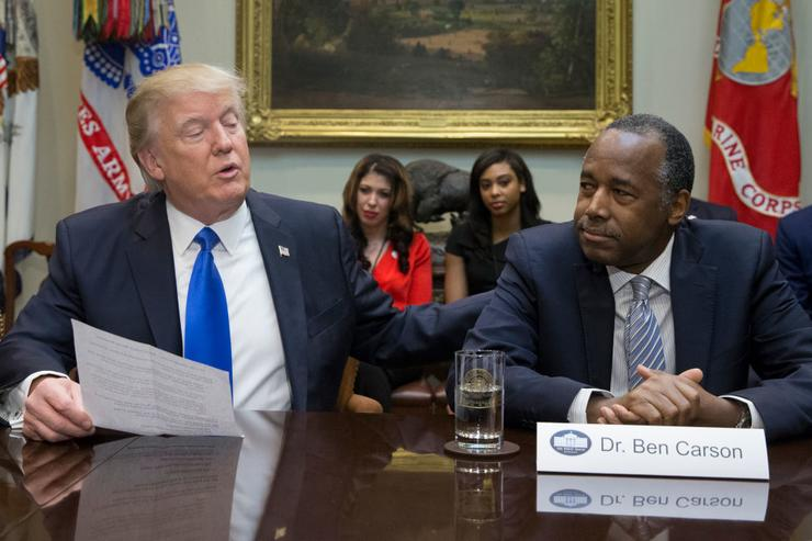 President Donald Trump (L), holds an African American History Month listening session attended by nominee to lead the Department of Housing and Urban Development (HUD) Ben Carson (R) and other officials in the Roosevelt Room of the White House on February 1, 2017 in Washington, DC.